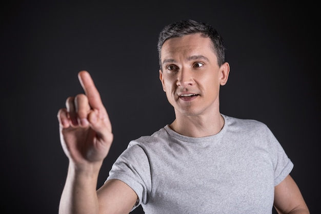 Tecnologia informática. homem bonito e inteligente, positivo, de pé na frente da tela e pressionando-a enquanto usa um novo dispositivo tecnológico