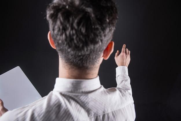Tecnologia informática. homem jovem e agradável em pé com um tablet e olhando para a mão enquanto toca a tela sensorial