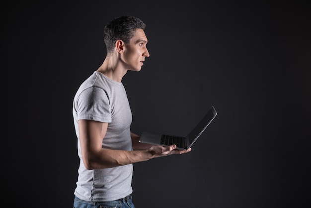 Tecnologia inteligente. homem simpático e confiante, animado, segurando seu laptop e olhando para a tela do laptop enquanto usa tecnologia inteligente