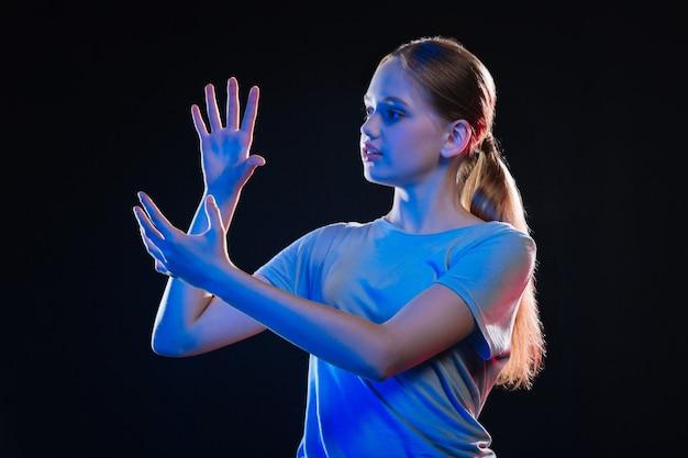 Tecnologia inteligente. jovem simpática olhando para as próprias mãos enquanto usa tecnologia virtual