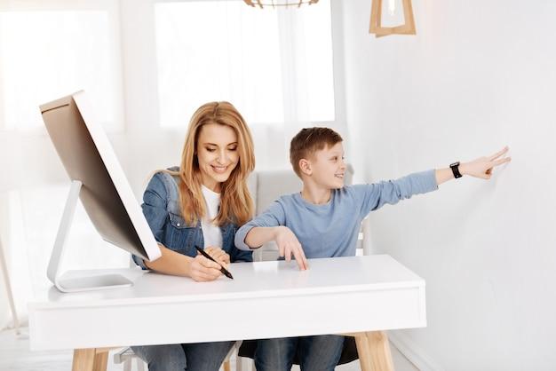 Tecnologia inteligente. menino feliz e positivo sentado à mesa sorrindo enquanto toca a parede