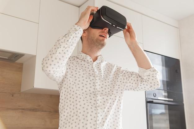 Tecnologia, jogo, entretenimento e conceito dos povos - homem novo feliz com os auriculares da realidade virtual ou os vidros 3d que jogam o jogo de vídeo.