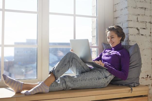 Tecnologia, lazer, diversão e relaxamento. jovem encantadora vestindo jeans elegantes e gola olímpica relaxando no parapeito da janela em casa com um computador portátil no colo