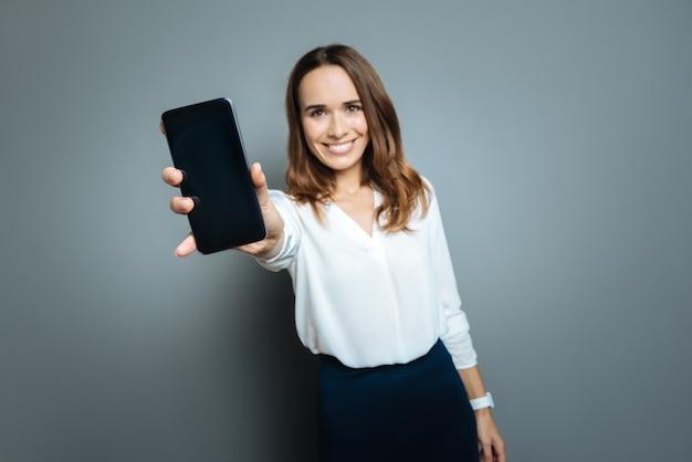 Tecnologia mais recente. mulher feliz, positiva e animada segurando seu smartphone e mostrando a você enquanto sorri