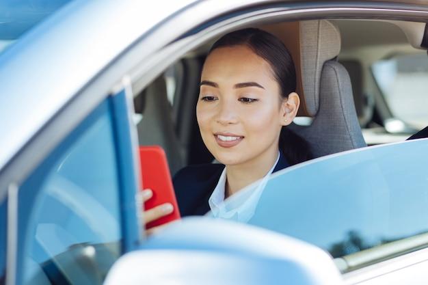 Tecnologia moderna. bela jovem segurando seu smartphone enquanto está sentado ao volante