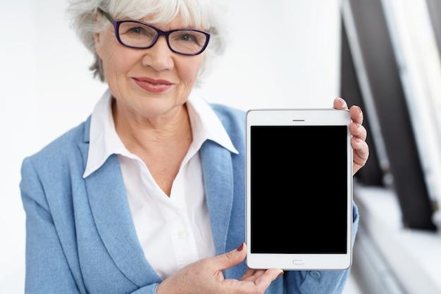 Tecnologia moderna, envelhecimento e conceito de comunicação online. mulher de negócios atraente, feliz e madura de sessenta anos com óculos elegantes, sorrindo e segurando um tablet digital com tela em branco