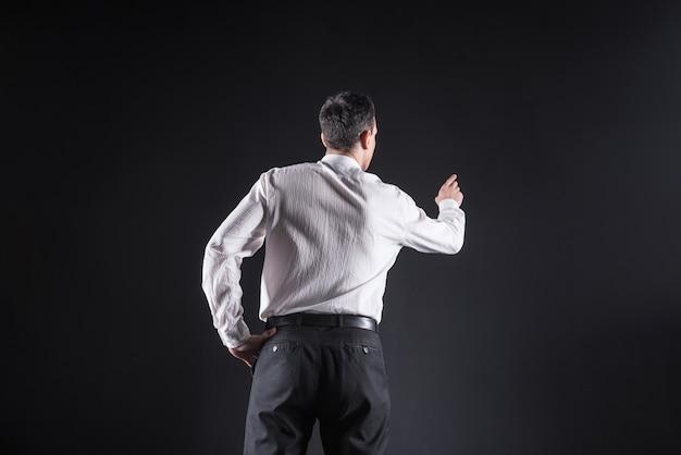 Tecnologia moderna. homem simpático e confiante em pé na frente da tela do computador e segurando sua mão enquanto a toca