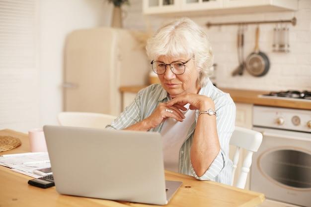 Tecnologia moderna, idosos e aposentadoria. aposentada feminina de cabelos grisalhos de óculos preenchendo o formulário de pedido de empréstimo online, sentada em frente ao laptop, lendo informações com olhar sério e focado