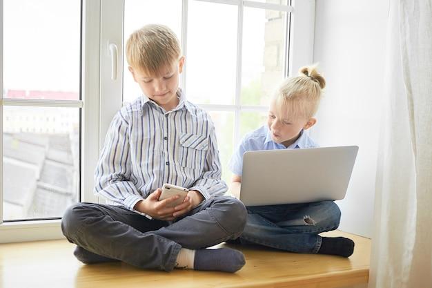 Tecnologia moderna, infância e conceito de aprendizagem. foto interna de dois irmãos mais novos sentados no parapeito da janela com as pernas cruzadas usando dispositivos eletrônicos, vestidos com camisetas e jeans