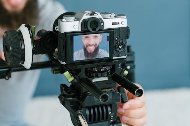 Tecnologia moderna para gravação de fotos e vídeos. câmera no tripé. equipamento e ferramentas do blogger. imagem de um homem na tela.