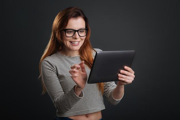 Tecnologia moderna. senhora experiente, criativa e ambiciosa, passando as páginas do tablet enquanto lê algo e parece fascinada