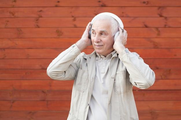 Tecnologia, povos e conceito do estilo de vida - homem superior feliz nos fones de ouvido que escuta a música, homem de negócios superior bem sucedido.