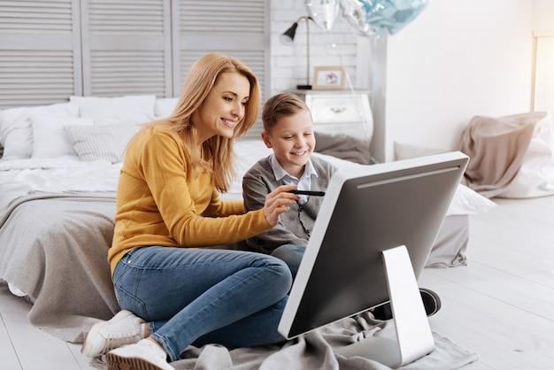 Tecnologia progressiva. mulher jovem, positiva e encantada, sentada junto com seu filho, sorrindo enquanto mostra a ele novas tecnologias