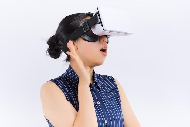 Tecnologia, realidade virtual, entretenimento e conceito dos povos - jovem mulher feliz com auriculares da realidade virtual ou vidros 3d e fones de ouvido