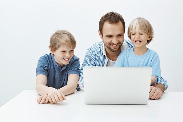 Tecnologia une família. retrato de um lindo pai feliz e filhos sentados perto do laptop e sorrindo amplamente, se divertindo