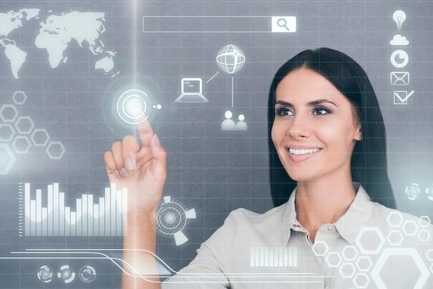 Tecnologias futuristas. mulher jovem confiante tocando uma tela transparente e sorrindo