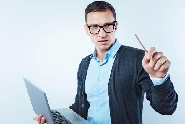 Tecnologias inovadoras. cavalheiro atencioso com uma caneta focalizando sua atenção em uma parede transparente enquanto trabalha em um projeto e usa seu laptop.