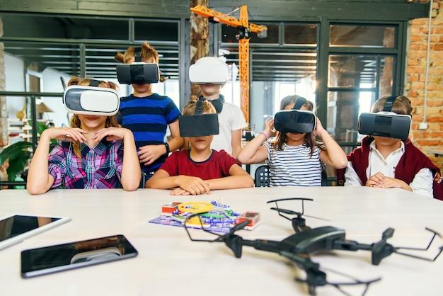 Tecnologias modernas em uma escola inteligente. alunos caucasianos inteligentes usam óculos de realidade virtual para a educação.