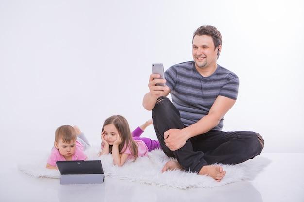Tecnologias modernas na vida cotidiana: um homem fala ao telefone através de um fone de ouvido, as crianças assistem a um desenho animado em um tablet.