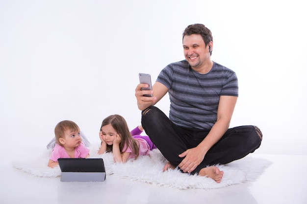 Tecnologias modernas no dia a dia: um homem fala ao telefone por meio de um fone de ouvido, as crianças assistem a um desenho animado em um tablet. hobbies e recreação com gadgets. pai com meninas no chão