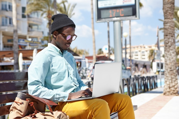 Tecnologias modernas, pessoas e estilo de vida urbano. atraente jovem blogueira afro-americana trabalhando em novo artigo usando pc notebook genérico durante as férias na cidade turística, inspirando o visual