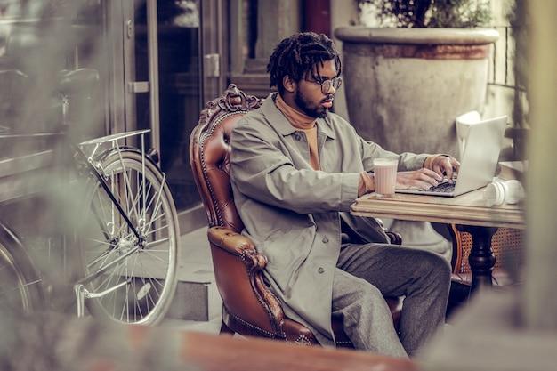 Tecnologias modernas. trabalhador internacional sério sentado em semi-posição e usando seu laptop