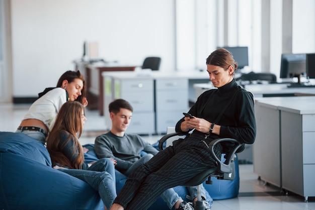 Tecnologias sem fio. grupo de jovens com roupas casuais, trabalhando em um escritório moderno