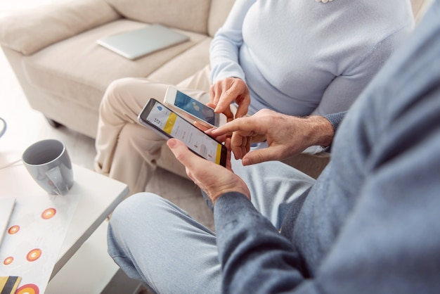 Tecnologias úteis. o close-up de um casal idoso sentado na sala de estar e verificando a previsão do tempo em seus telefones, comparando-as