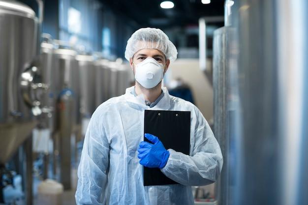 Tecnólogo com máscara protetora e rede para o cabelo em pé na linha de produção da fábrica