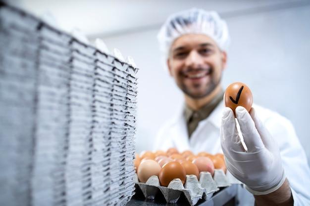 Tecnólogo de fábrica de alimentos parado ao lado da máquina industrial de classificação de ovos e segurando um ovo que passou no teste de controle de qualidade.