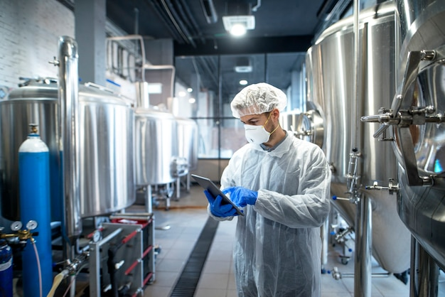 Tecnólogo em uniforme protetor branco controlando o processo industrial usando computador tablet