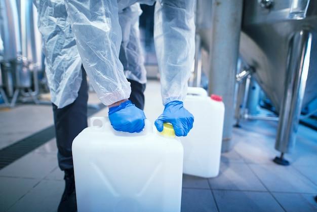 Tecnólogo trabalhador industrial irreconhecível com luvas protetoras de borracha, abrindo uma lata de plástico com produtos químicos na fábrica.
