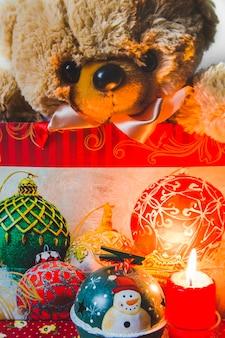 Teddybear na sacola de compras com enfeites de natal decorativos e vela acesa