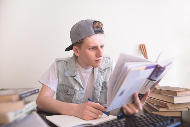 Teen lê um livro com cuidado e escreve em um caderno.