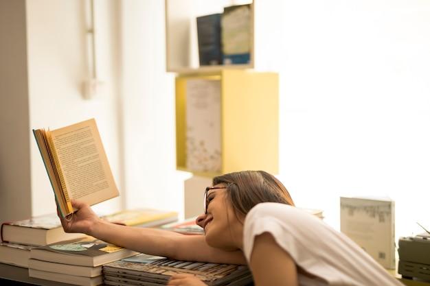 Teen schoolgirl lendo sobre pilha de livro