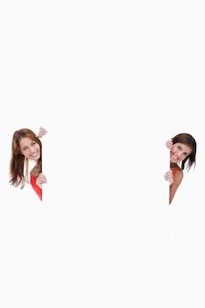 Teenage girls olhando a câmera enquanto segurava um cartaz em branco