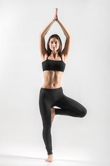 Teenager girl in yoga tree pose