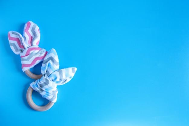 Teether bonito orgânico do coelho de coelho do bebê no fundo azul com espaço da cópia.