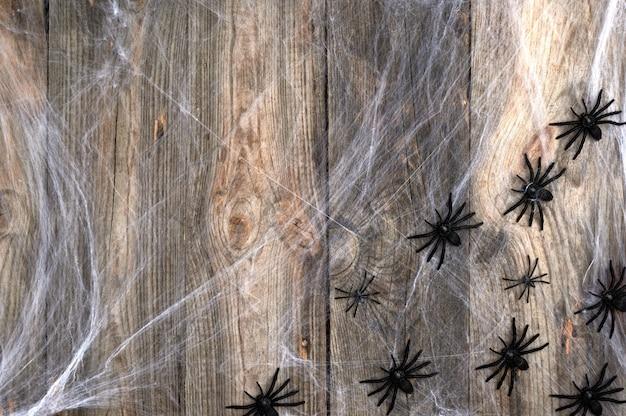 Teia de aranha branca com aranhas negras em um cinza de madeira de tábuas velhas, pano de fundo para o feriado halloween