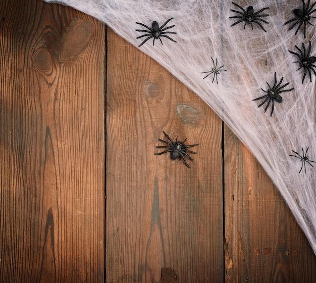Teia de aranha branca com aranhas negras sobre um fundo de madeira de tábuas velhas