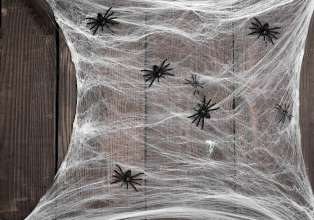 Teia de aranha branca com aranhas pretas em um fundo de madeira