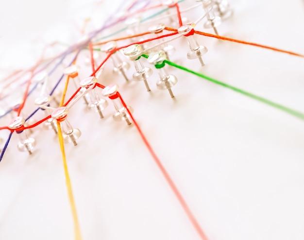 Teia de fios vermelhos, verdes e amarelos sobre fundo branco