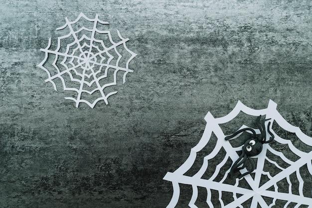 Teia de papel com aranha de brinquedo em fundo cinza