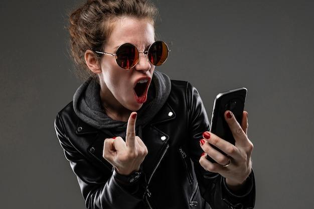 Teimosa garota caucasiana com características faciais ásperas em uma jaqueta preta mostra seu telefone e não gosta isolado na parede preta