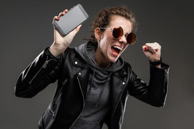 Teimosa garota caucasiana com características faciais ásperas em uma jaqueta preta mostra seu telefone e se alegrou isolado na parede preta