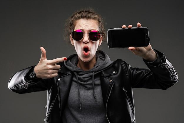 Teimosa garota caucasiana com características faciais ásperas em uma jaqueta preta mostra seu telefone isolado na parede preta