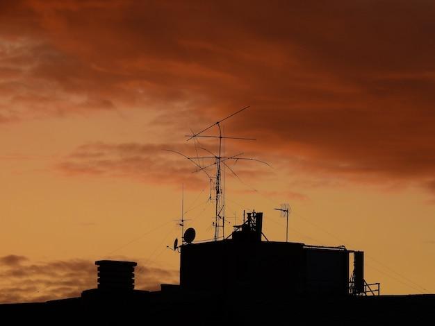 Tejados chimeneas y antenas de telecomunicaciones en contraste com el cielo anaranjado al anochecer