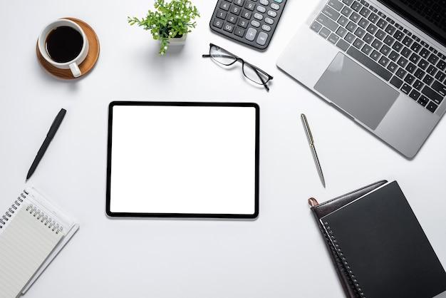 Tela branca em branco do tablet digital com muitos dispositivos de tecnologia colocados na vista superior de mesa branca.