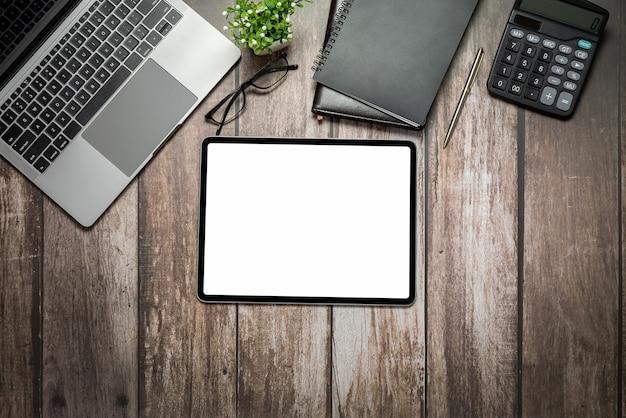 Tela branca em branco do tablet digital e calculadora do notebook com teclado no antigo espaço de cópia da mesa de madeira