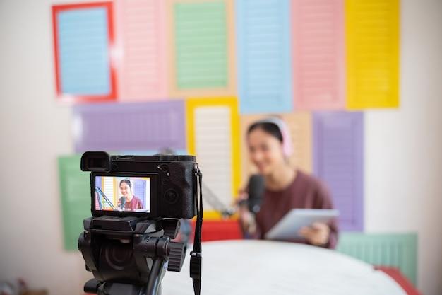 Tela de câmera digital com tripé gravando um podcast de menina